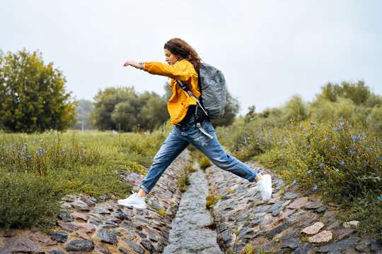 Young girl traveler jumps over a stream
