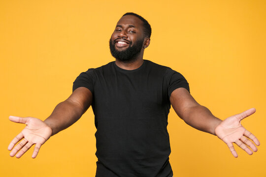 Smiling african american man guy football fan in casual black t-shirt isolated on yellow background studio. People lifestyle concept. Mock up copy space. Standing with outstretched hands for hugs.