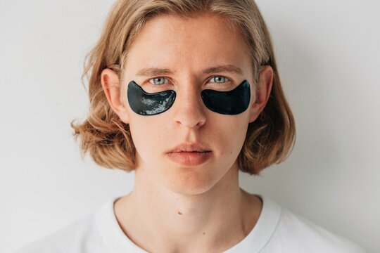 Young blond man with black eye patches