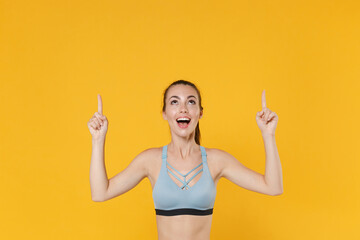 Excited young fitness sporty woman girl in sportswear working out isolated on yellow wall...