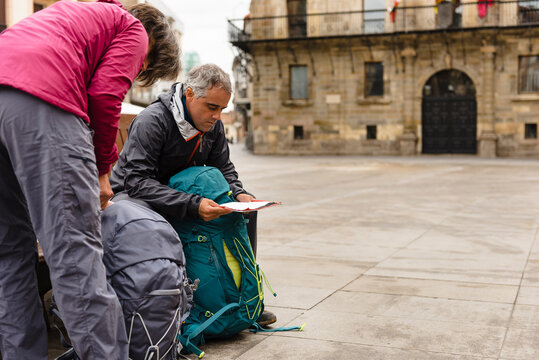 Couple of pilgrims seated in a bench reading a map in Astorga City on their way to Santiago de Compostela
