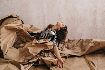 Creative carefree woman emerging from pile of craft paper