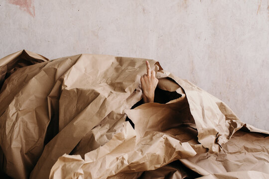 Person covered with pile of craft paper sticking out hand with fuck gesture