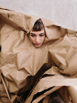Creative serious woman peeking out pile of craft paper