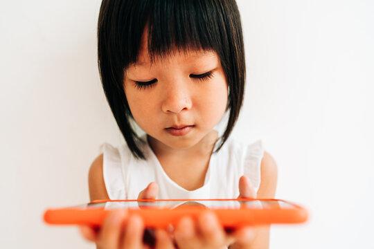 portrait of little girl using cell phone