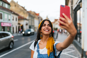 Close up of a beautiful smiling young woman taking selfie.