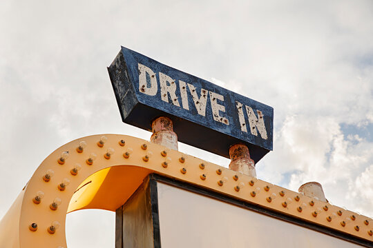 Close up of neon Drive In sign during the day with clouds in the background
