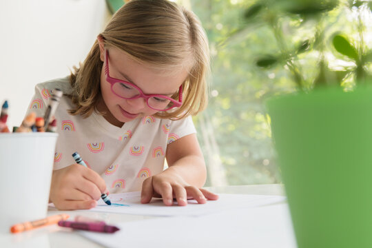 Little girl with down syndrome coloring