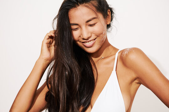 Stunning Asian Woman Smiling Portrait - Sun protection concept - Beach salty hair with Sand on Skin