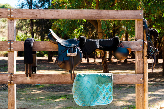 Horse saddle in a wooden fence