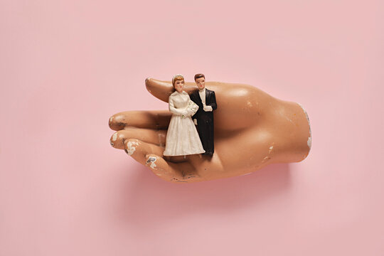 vintage wedding cake figurines held in a hand on a pink background