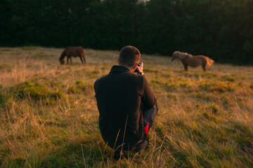photo of a photographer from behind who takes pictures of grazing horses