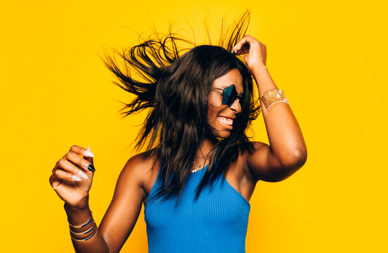 Excited happy Afro Woman posing over yellow background moving her hair