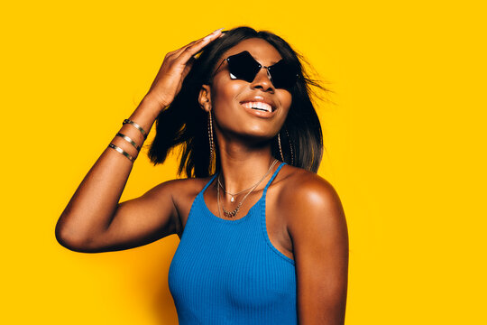 Happy Afro Woman posing over yellow background moving her hair