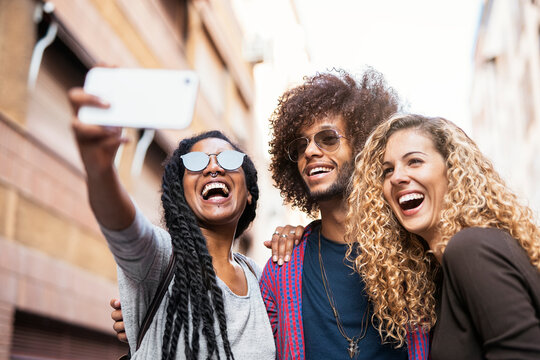 Multiethnic friends group taking selfie with mobile phone