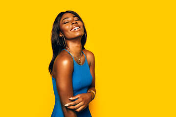 Happy Black Woman posing over yellow background