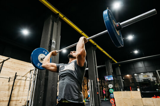 Athletic man doing a clean and jerk in a crossfit box