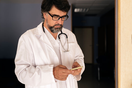 Portrait of a doctor looking at his phone