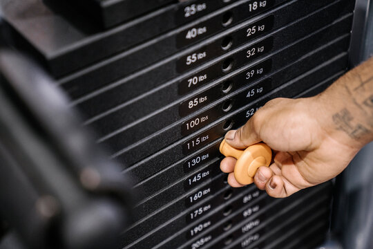 Close up of a man's hand holding a weight stack.