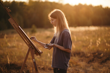 Woman drawing in nature in evening