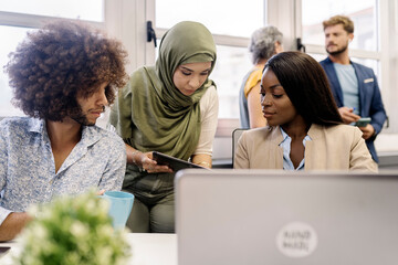 muslim woman in hijab, a african woman and curly hair man working together in the office using laptop.