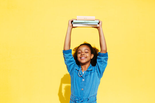 Glad black girl holding textbooks in raised arms