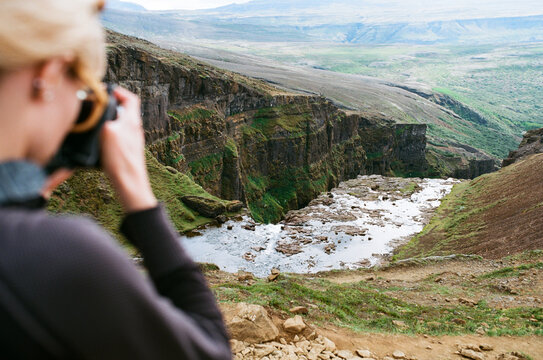 Woman taking picture of a landscape on the top of Glymur waterfall in Iceland