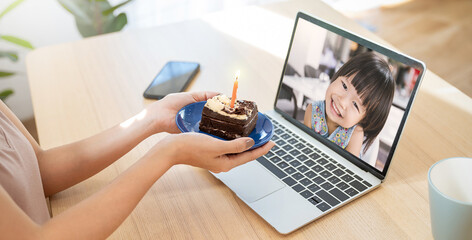 Asian family mother daughter celebrates birthday via the internet in quarantine time, self isolation family values, online birthday virtual party with cake, family online in video conference.
