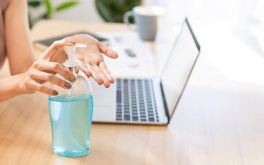 Hands using sanitiser alcohol bottle antibacterial gel rub clean hands, hygiene prevention of virus outbreak. closeup bottle of antibacterial sanitiser soap on desk with laptop, new normal coronavirus