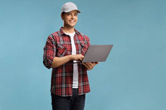 Young man in a shirt holding a laptop computer and looking at the camera
