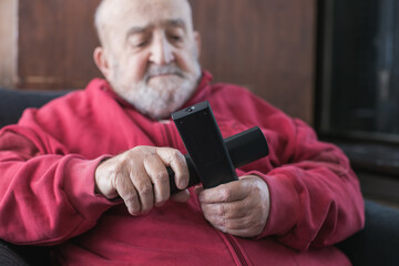 old man confused with tv remote controls