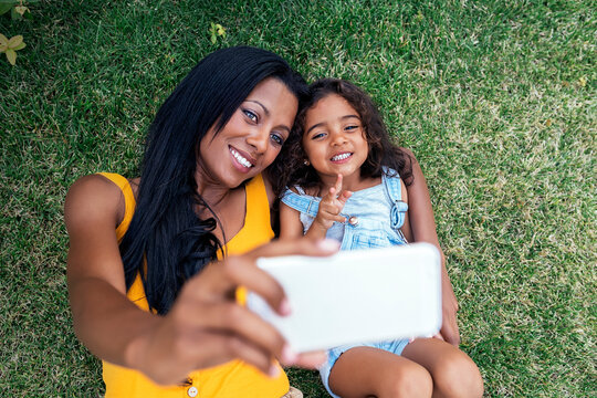 Beautiful woman with her cute daughter taking selfie