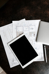 Workplace of modern engineer with tablet, plans and maps.