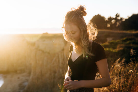 Beautiful teen by the ocean at sunset