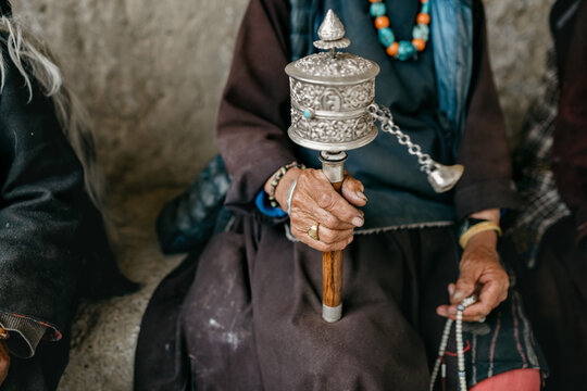 Close up of old woman holding prayer wheel
