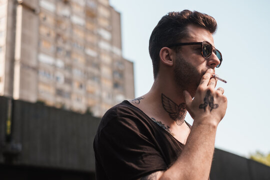 Tattooed Man Smoking A Cigarette On The Street