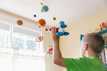 Child in Bedroom Playing Astronaut with Toy Rocket Ship and Solar System Mobile