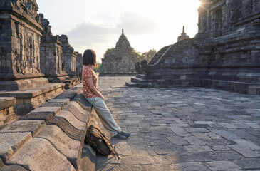 Foto op Canvas Historisch mon. Woman with backpack enjoying the sunset in Prambanan Temple, Java, Indonesia