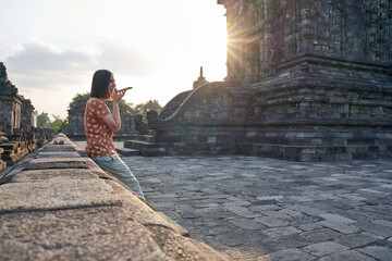 Foto op Canvas Historisch mon. Woman using cell phone at sunset in Prambanan Temple, Java, Indonesia