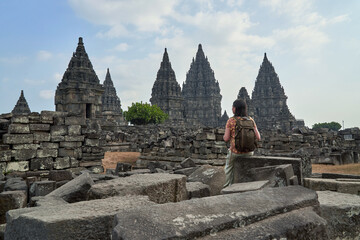 Foto op Canvas Historisch mon. Back view of woman with backpack looking at a stupa in Prambanan Temple, Java, Indonesia