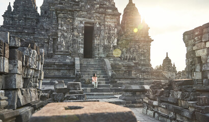 Foto op Canvas Historisch mon. Woman with backpack sitting at the steps of the temple's entrance. in Prambanan Temple, Java, Indonesia
