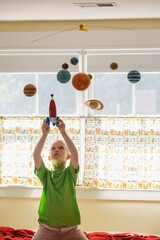 Child Astronaut Blast off with Toy Rocket Ship and Solar System Mobile