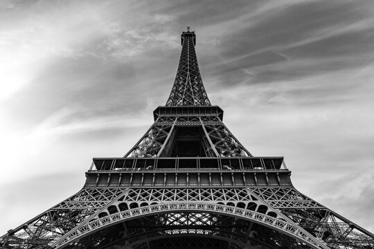 Black and White Image Of The Eiffel Tower Against Wispy Sky