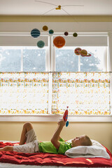 Creative Child Playing Astronaut with Toy Rocket Ship and Solar System Mobile