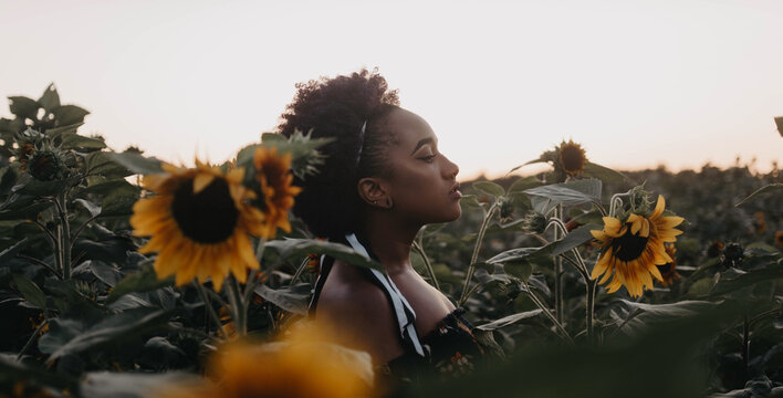 A beautiful young black woman standing in a field of flowers