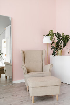 Modern pink interior with mirror and beige chairs for relax.
