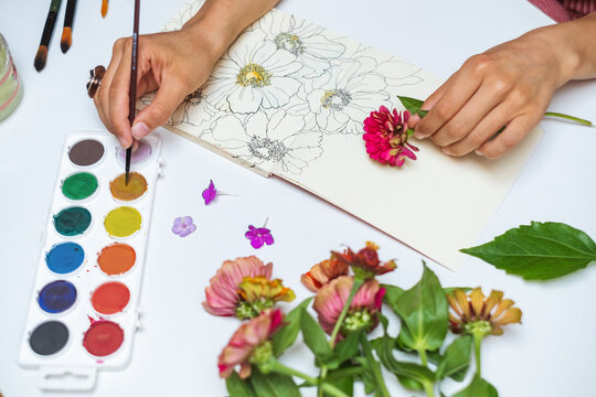Anonymous female artist painting flowers with watercolors