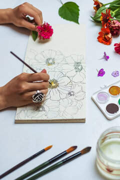 Anonymous female artist painting flowers with watercolors on a sketch pad