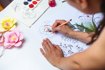 Anonymous female artist drawing flowers on a piece of paper