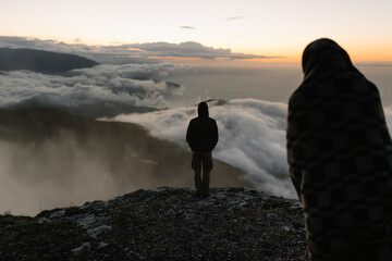 Couple stands on the edge of cliff above the clouds at dawn